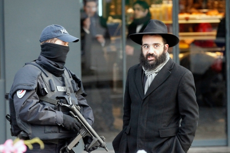 Eternal Return of the Same? Police officer talks to a Jewish person outside the kosher grocery where Amedy Coulibaly killed four people earlier in a terror attack, in Paris, Tuesday, Jan. 20, 2015.