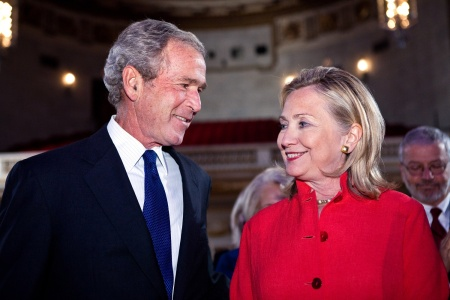 Bush: 'I think I killed even more Iraqi than Bill. And now I am getting richer everyday with the oil price shooting up.' Clinton:'Stop bragging, we got things rolling with our blockade of Iraq. Bill and me killed hundreds of thousands from our blockade of drugs going into Iraq.'